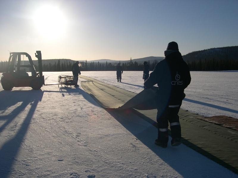 Les balloniers déroulent un long tapis protecteur avant l'opération délicate de dépliage du ballon principal. Crédits : CNES/N. Journo, 2004