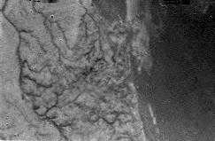 A 16 km d'altitude, une région claire et complexe et une région sombre et lisse. On y distingue ce qui ressemble à un réseau fluvial et à un littoral. Il est trop tôt pour dire si un liquide est présent à la surface. Crédit : ESA/NASA/Univ....