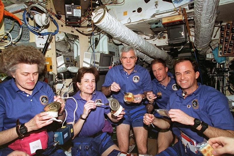L'équipage amériacain de la mission STS-76 partage un repas russe avec les cosmonautes de la station MIR ; crédits Nasa