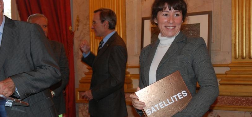 Fadela Amara, secrétaire d'Etat à la politique de la Ville, avec dans les mains de tout dernier ouvrage du CNES intitulé « Satellites ». Crédits : CNES.